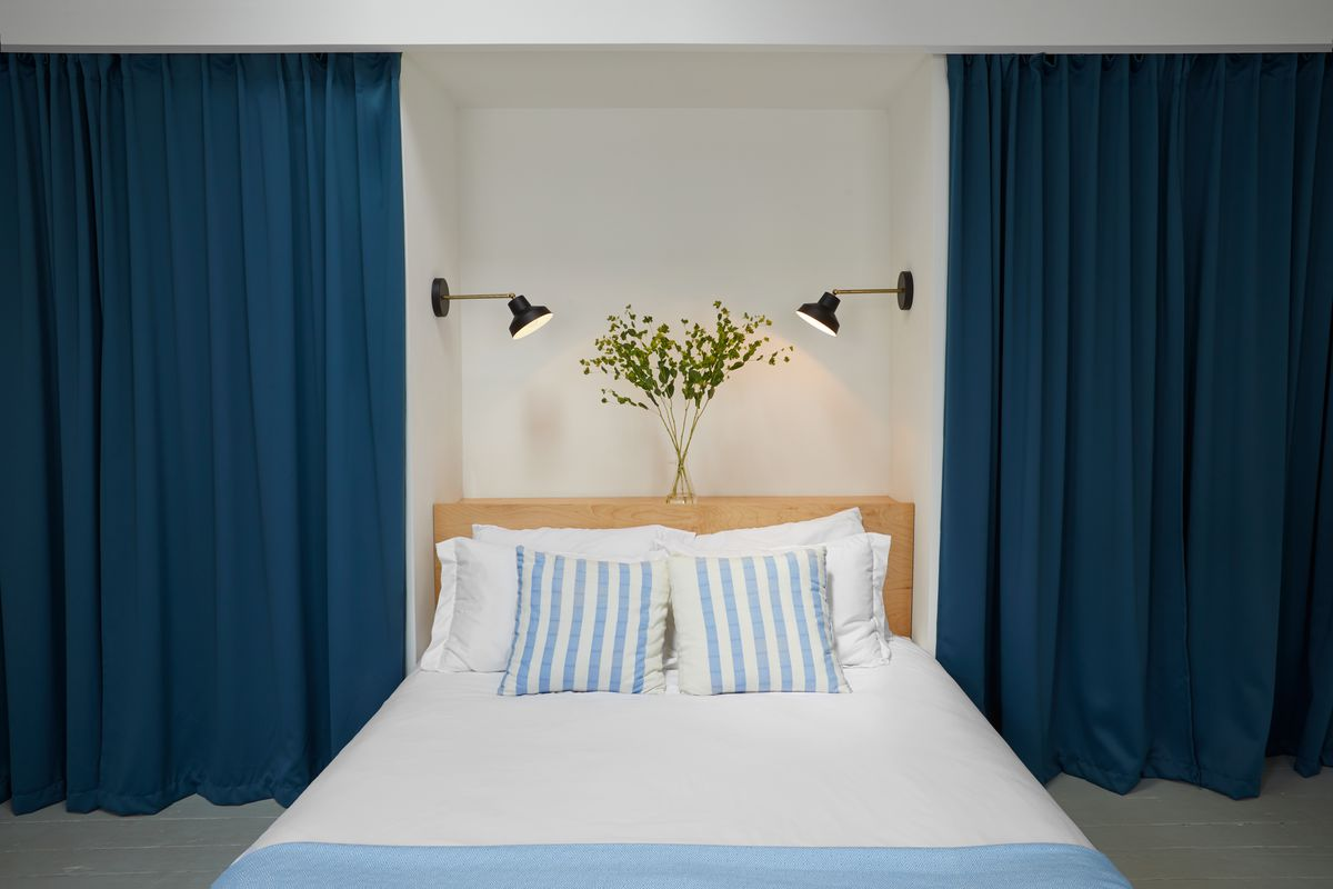 A bedroom. There is a large bed with white bed linens and multiple assorted pillows. There are dark blue floor to ceiling curtains that are on both sides of the bed. There is a plant in a vase on the bed's headboard. Two black light fixtures hang above th