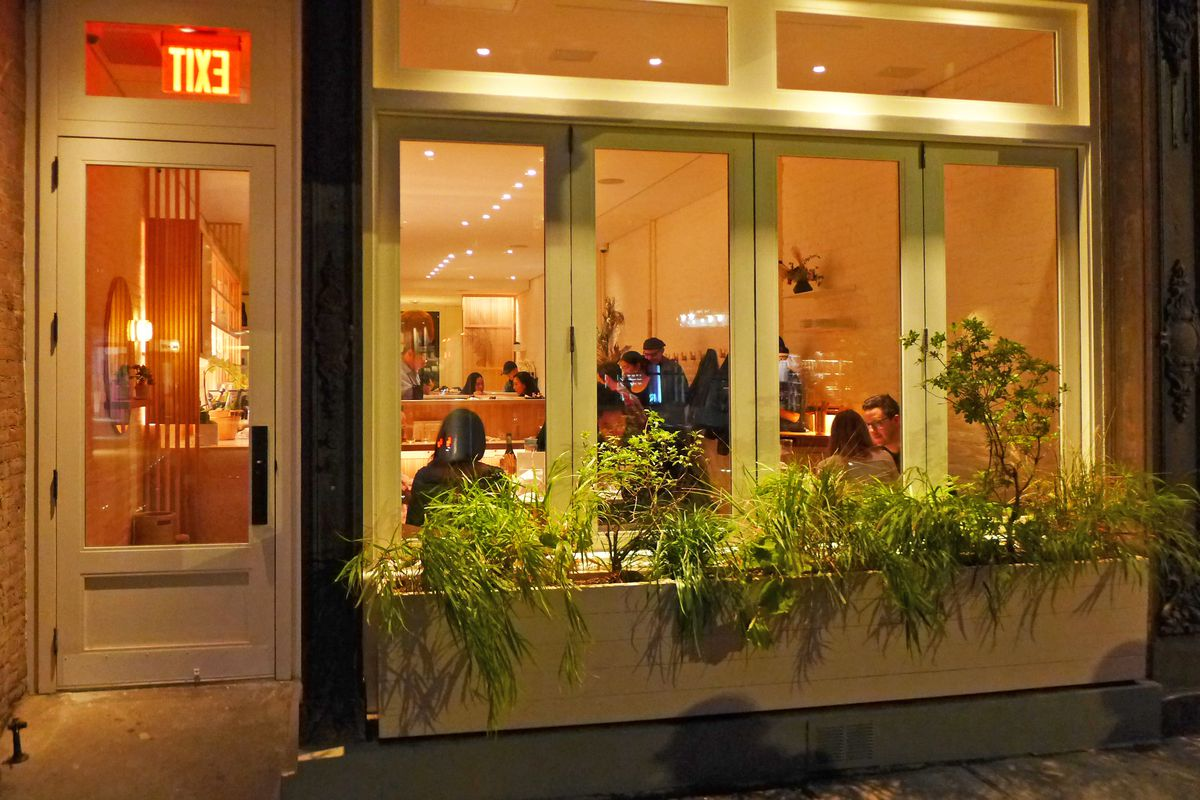 Exterior of the restaurant in the evening, with lights shining through the window and some seated customers inside...