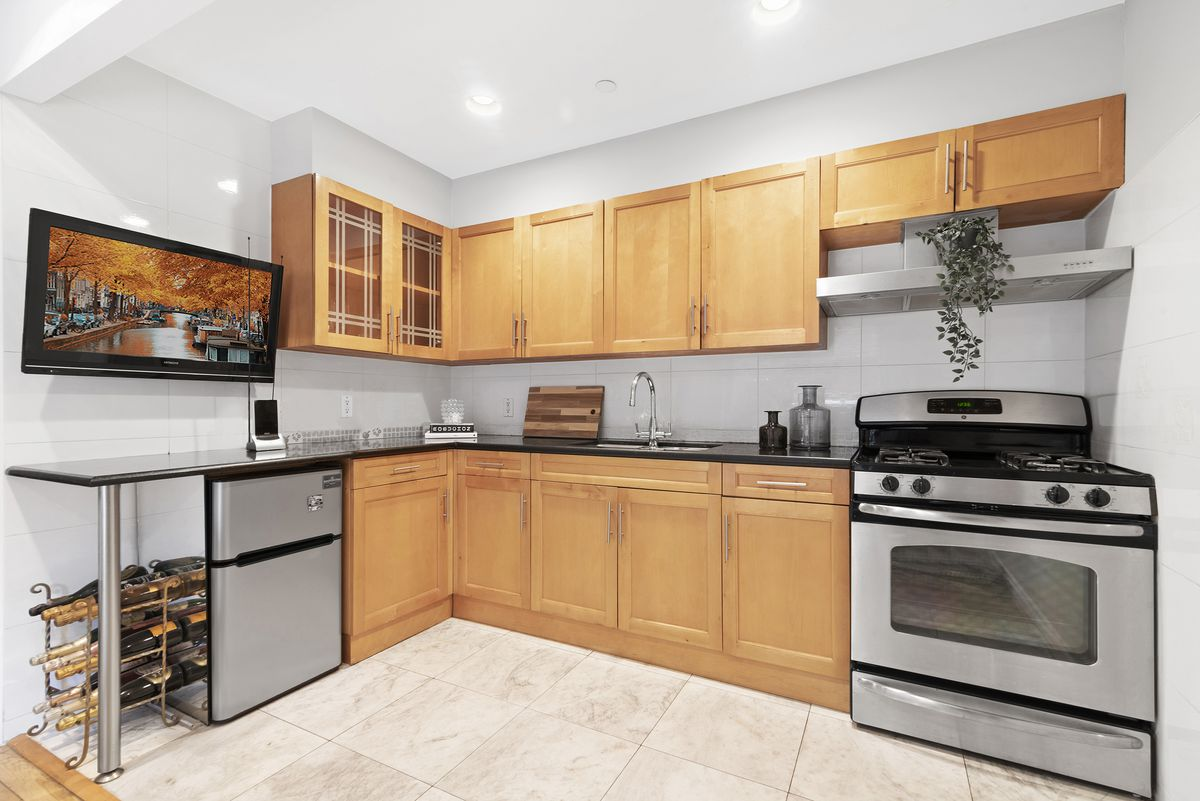 A kitchen with wooden cabinetry and beige tile floors.
