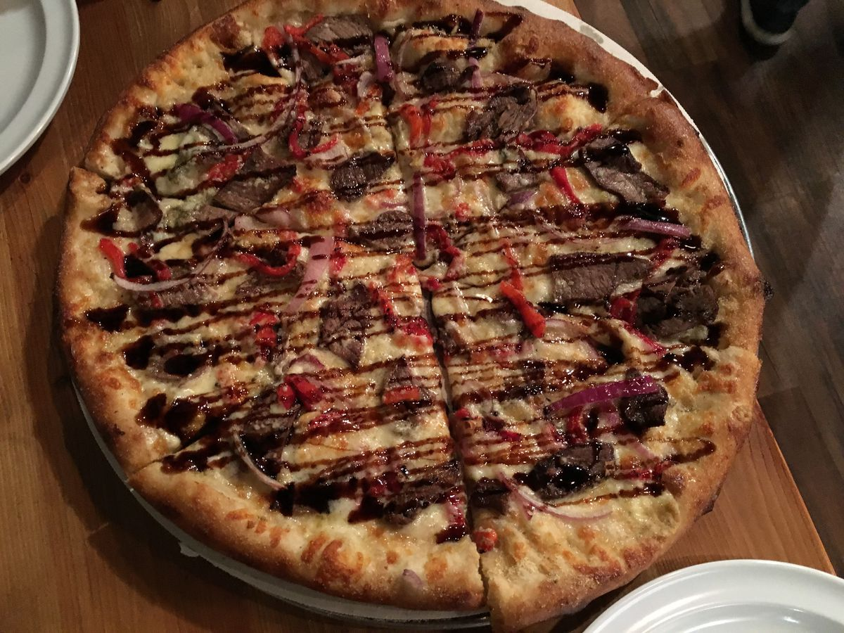 A beef pizza with bell pepper and a balsamic drizzle.