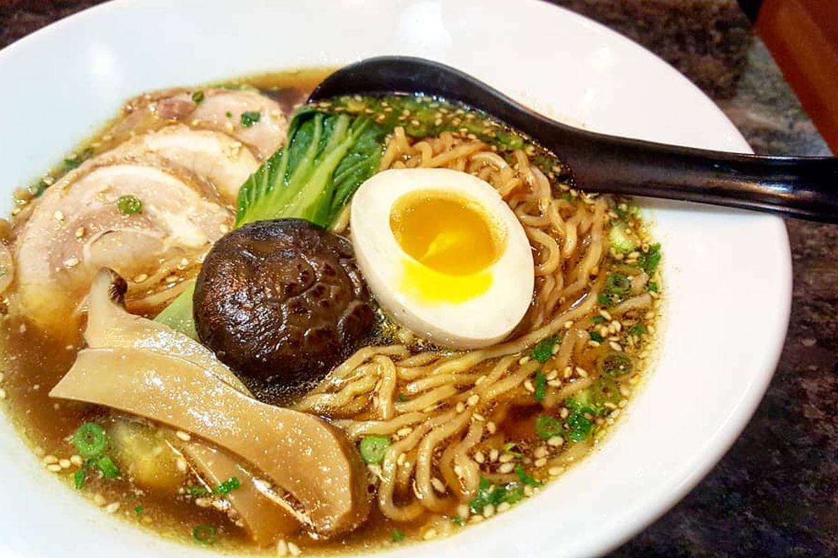 A bowl of ramen with an egg, noodles, mushrooms, and more