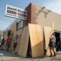 People board up Jewell Motors Used Cars Tuesday afternoon, Aug. 25, 2020, after a night of unrest following the shooting of Jacob Blake by a police officer in Kenosha Sunday.