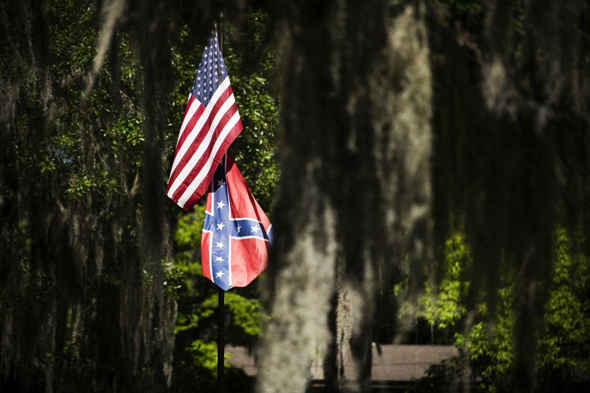 A US and CSA flag share a flagpole, the US one draped slightly over the Confederate one. They are framed by trees.