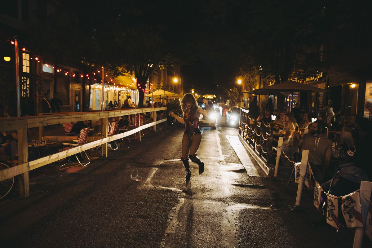 drag performer on street at night with tables set up on either side