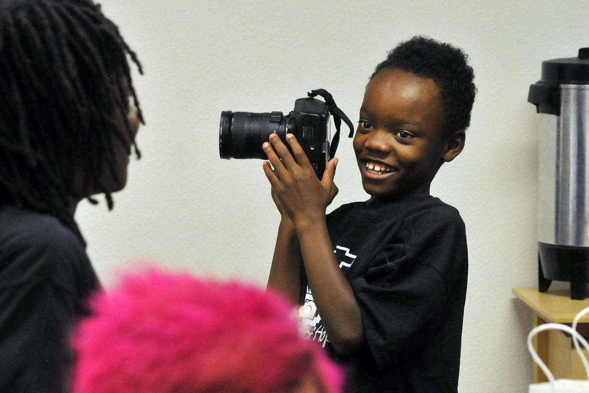"""In this photo taken Sept. 4, 2012, Darrionte Thomas smiles after he takes a photograph with Linda Solomon's camera while participating in the """"Pictures of Hope,"""" program at the Barrett Foundation, a program that helps homeless women and children in Albuqu"""