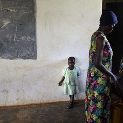 """In this photo taken Friday, April 27, 2012, Adye Sunday, 25, right, who was abducted when she was 13 by Lord's Resistance Army (LRA) leader Joseph Kony and forced to be one of his dozens of """"wives"""" and says he's also the father of her two children, one of whom Betty, 3, stands at left, prepares food to sell at a center set up to help those who have left or fled the LRA, in Gulu, Uganda. Adye Sunday isn't sure about the calls to kill or capture LRA leader Joseph Kony, who inspires conflicted thoughts among some people in northern Uganda, despite more than 3,000 children being abducted by the LRA since 2008, according to the U.N. and Human Rights Watch."""