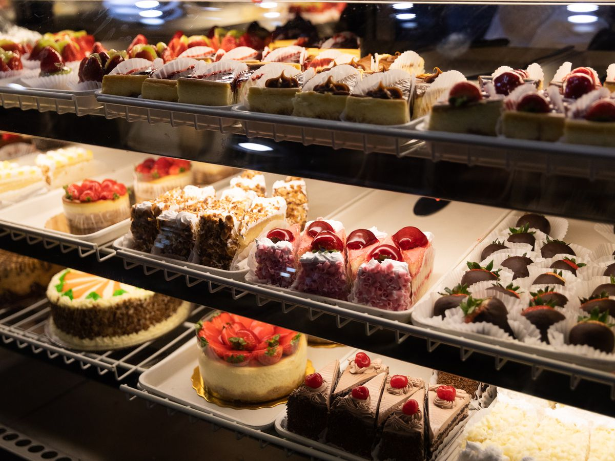 Whole and sliced cakes in a chilled deli case at Mexicantown Bakery.