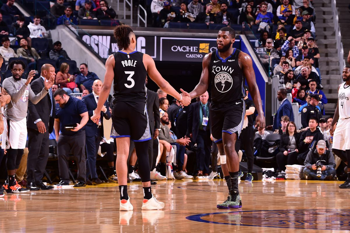 Jordan Poole #3 and Eric Paschall #7 of the Golden State Warriors hi-five during the game against the LA Clippers on March 10, 2020 at Chase Center in San Francisco, California.