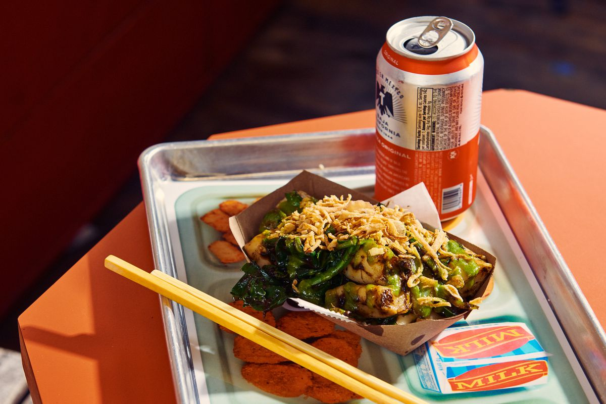 Rice rolls with with vegetables sit in a cardboard tray over a lunch tray in between a can of Tecate and a pair of chopsticks