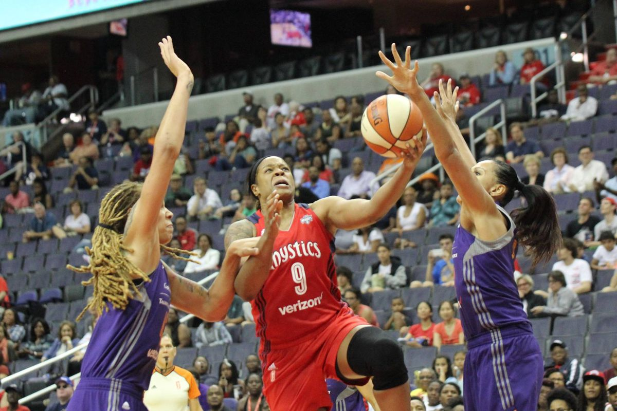 Kia Vaughn of the Washington Mystics attempts a layup as Mistie Bass and Brittney Griner defend her.
