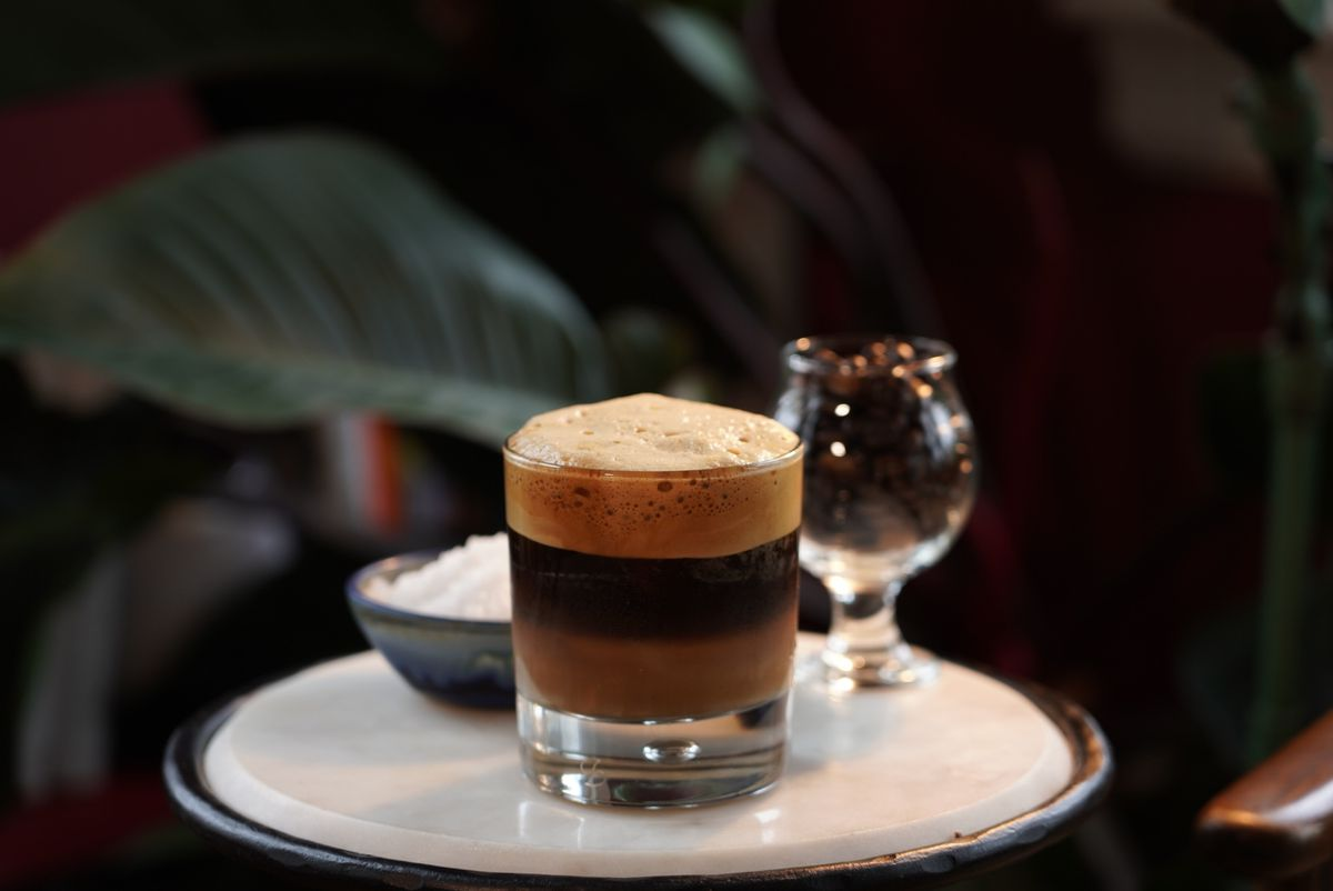 A glass of dark foam-topped coffee sits on a small white table with a glass of coffee beans and bowl of salt visible in the background