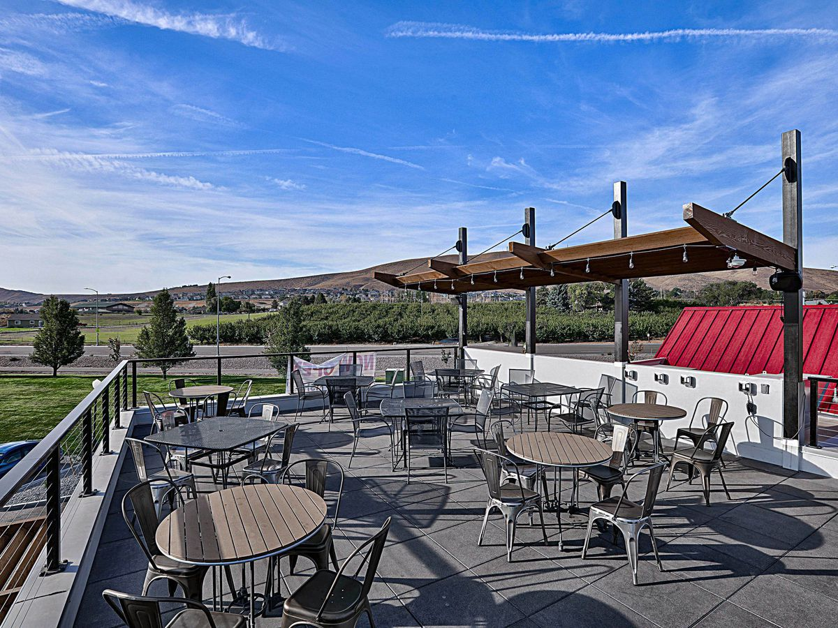 3 Eyed Fish Wine Kitchen and Bar's outdoor deck and patio with fields in the background, and empty tables and chairs