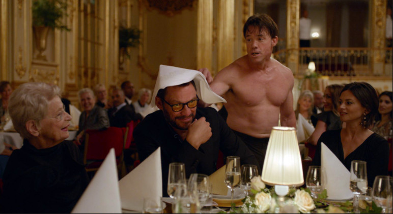 Terry Notary shirtless among tables of dressed-up people at a fundraiser in 'The Square'