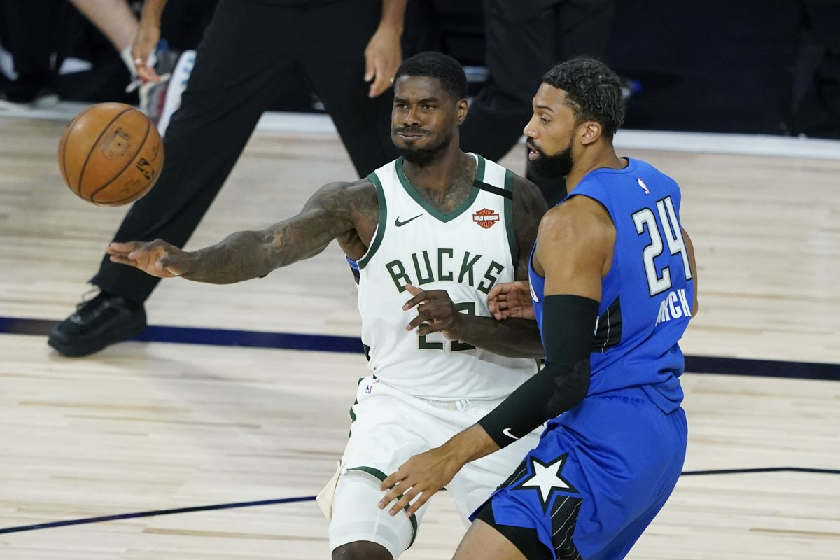 Marvin Williams of the Milwaukee Bucks passes the ball around Khem Birch of the Orlando Magic during the first half of an NBA basketball first round playoff game on August 20, 2020 in Lake Buena Vista, Florida.