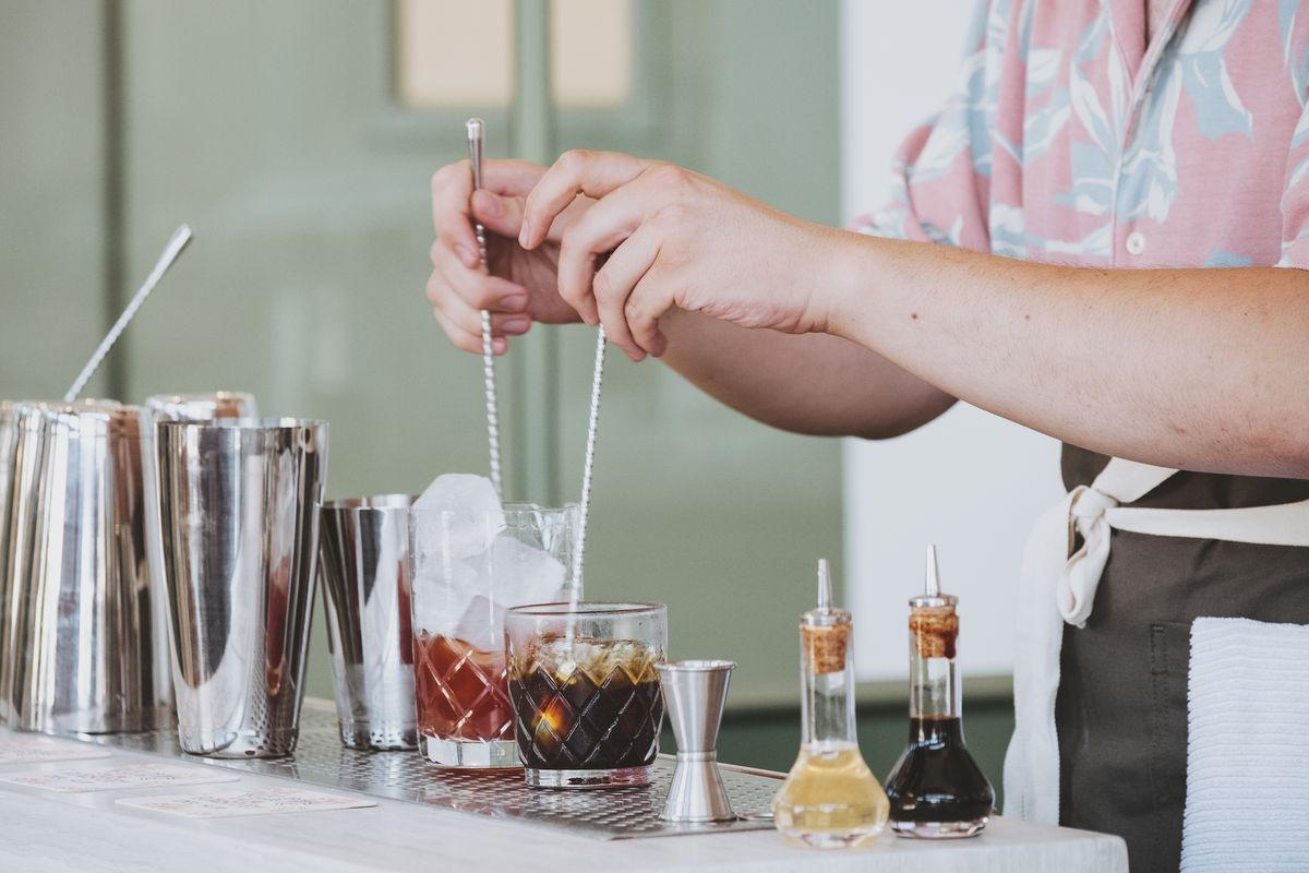 Coffee being stirred by a barista, as it looks like a cocktail being made.