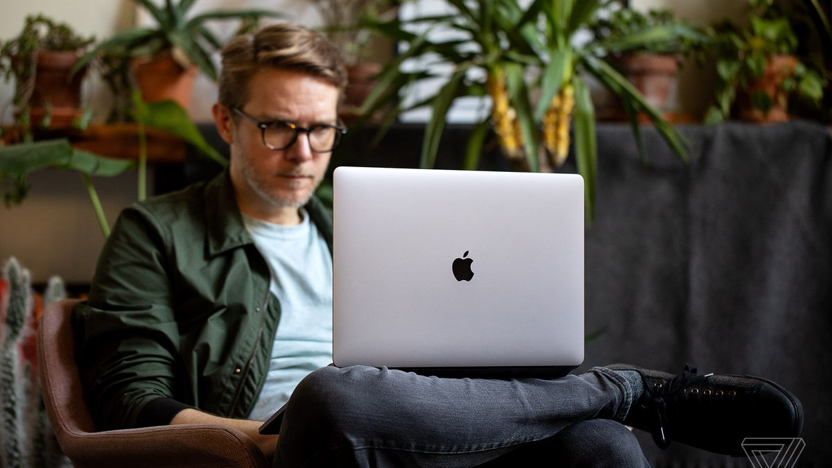 A user types on a MacBook Pro while seated in a chair.
