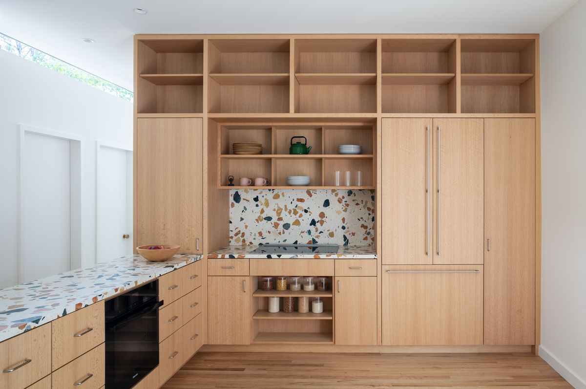 A full-height kitchen cabinet with terrazzo counters and backsplash and various shelves containing jars and other wares.