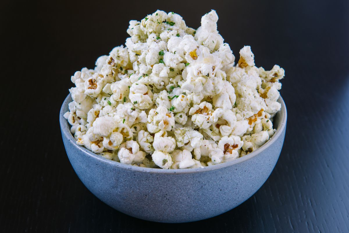 Popcorn with a green seasoning is piled high in a blue bowl, isolated on a black background.