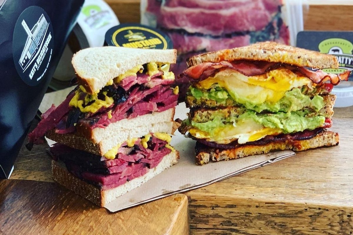 Two halves of a pastrami sandwich sit stacked next to two halves of an eggy breakfast sandwich