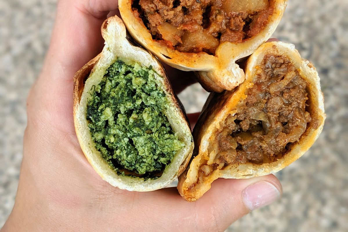 A hand holds three empanadas, cut open, including spinach, beef and potato, and chicken