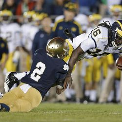 Michigan's Denard Robinson (16) is tackled by Notre Dame's Bennett Jackson (2) during the second half of an NCAA college football game Saturday, Sept. 22, 2012, in South Bend, Ind. Notre Dame defeated Michigan 13-6.