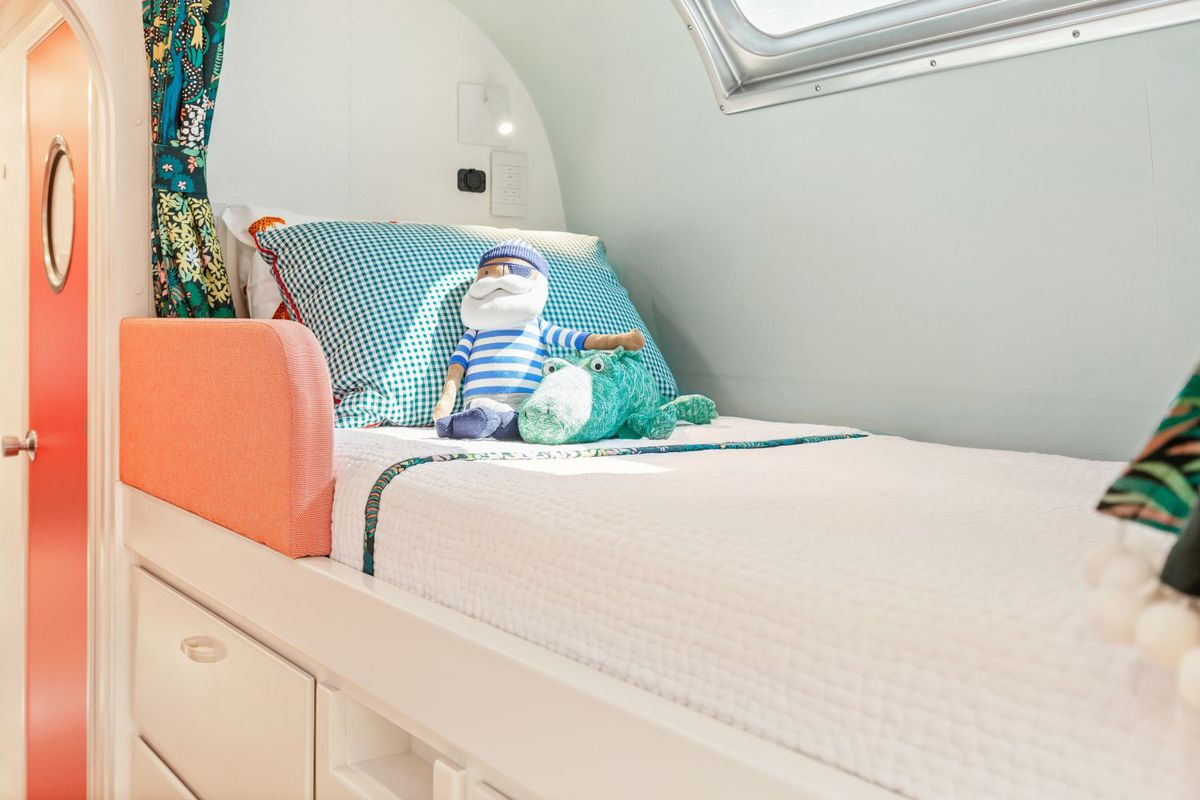 A closer up view of the bunk bed shows a white comforter, light teal walls, and a gingham pillow.