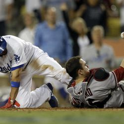 Arizona Diamondbacks catcher Miguel Montero, right, shows the umpire the ball after forcing Los Angeles Dodgers' Shane Victorino out at the plate during eighth inning of a baseball in Los Angeles, Saturday, Sept. 1, 2012.