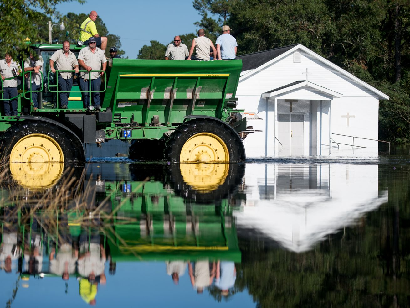 Workers use farm machinery to navigate floodwaters from the Waccamaw River caused by Hurricane Florence in Bucksport, South Carolina. Sea-level rise exacerbated flooding from the storm.