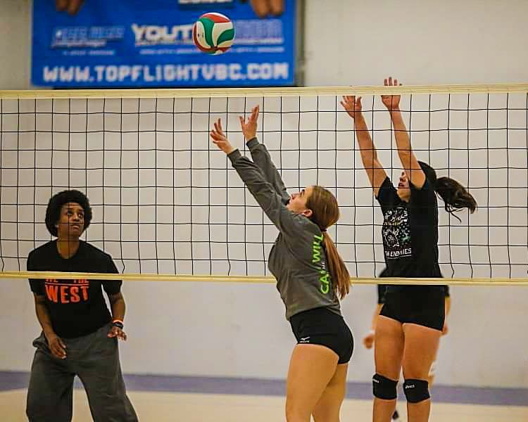 Tiana Theiss, center, setting the volleyball in a Players indoor ball game.