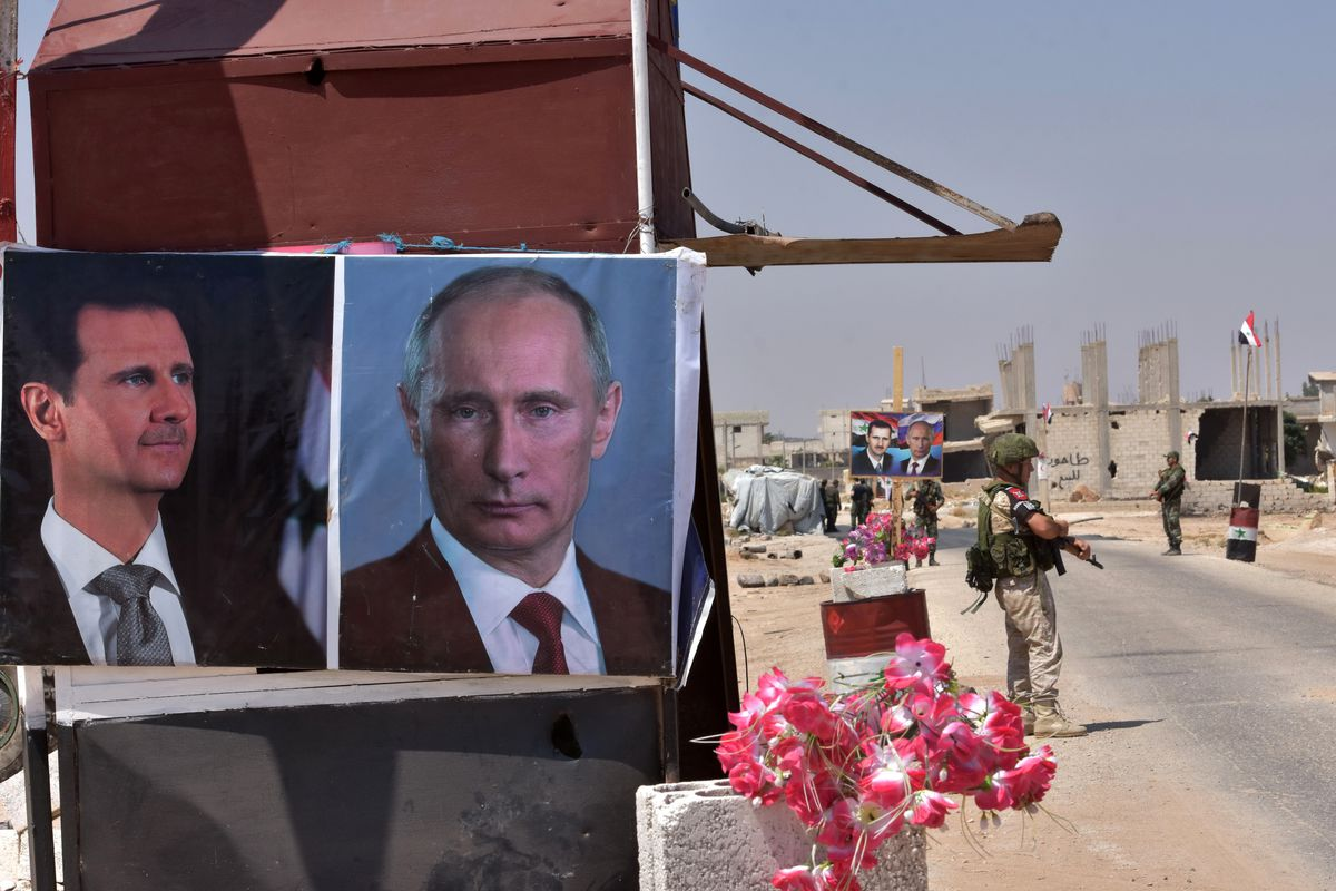 1cdb9eeb4968b1 Members of Russian and Syrian forces stand guard near posters of Syrian  President Bashar al-