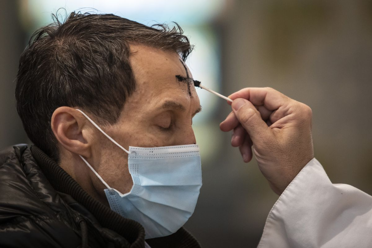 A congregant receives the imposition of ashes from Father Tom Hurley at Old St. Patrick's Catholic Church on the Near West Side on Ash Wednesday. Amid fears of the coronavirus pandemic, Hurley did not touch anyone and gave out ashes on a fresh Q-tip to each congregant, then threw the Q-tip away.