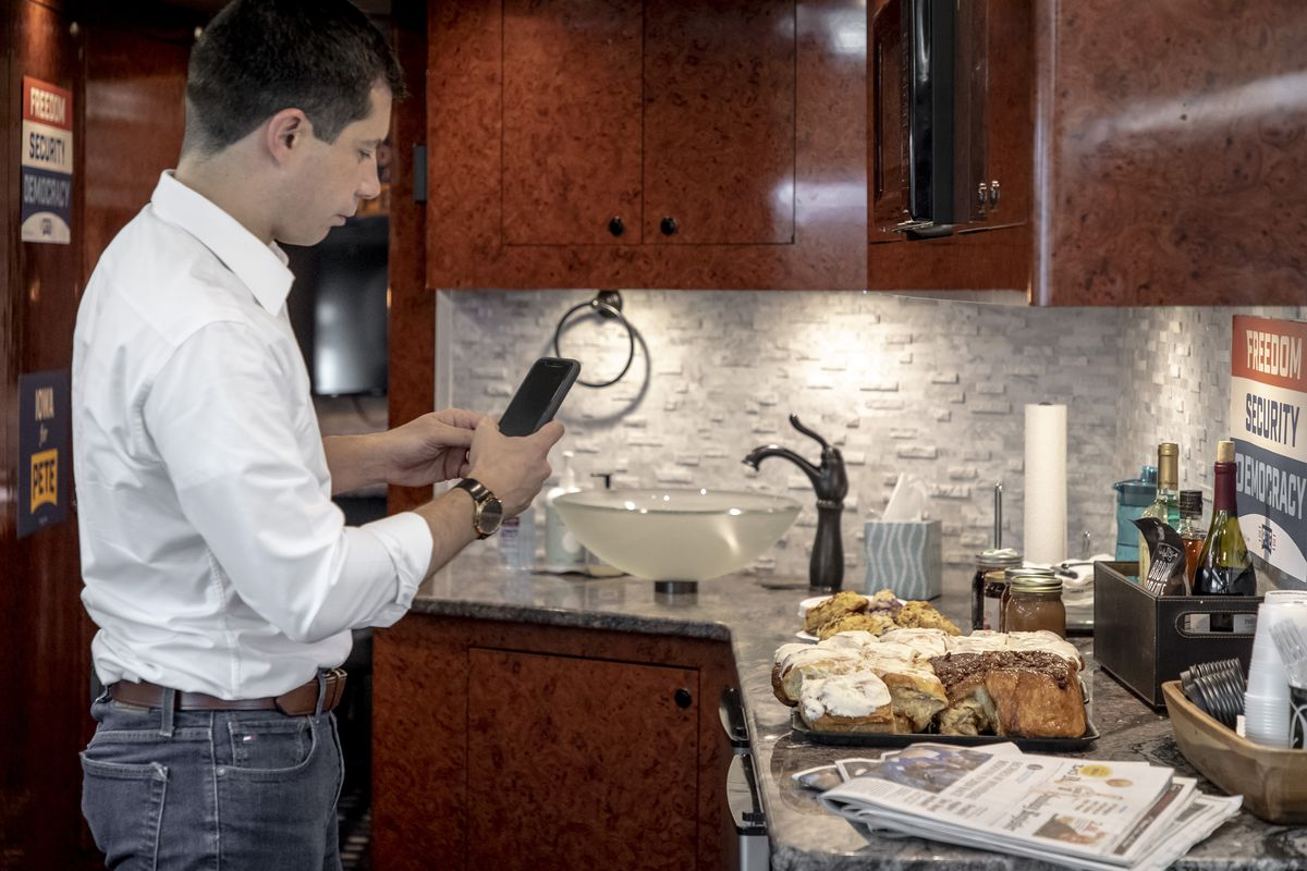 Buttigieg photographs cinnamon buns with his phone.