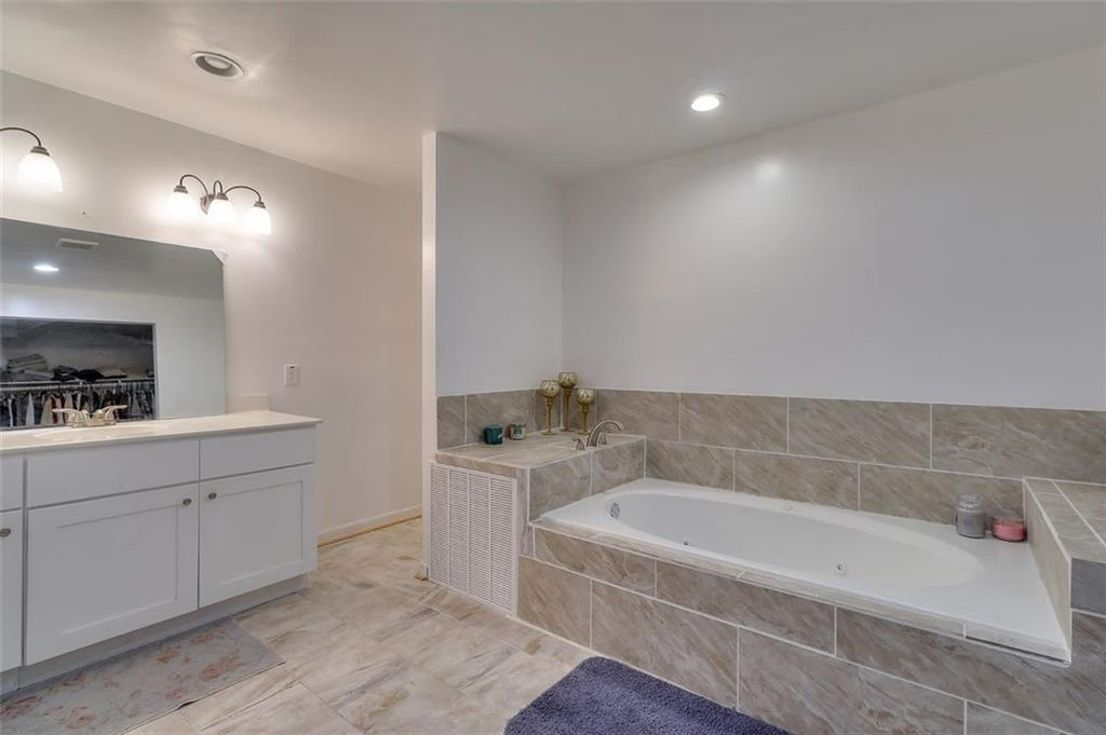 A white master bathroom with a large tub and mirror at left.