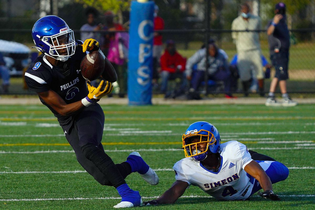 Phillips's Avante Savage (9) makes a catch with Simeon's Andre Crews (4) on the ground.