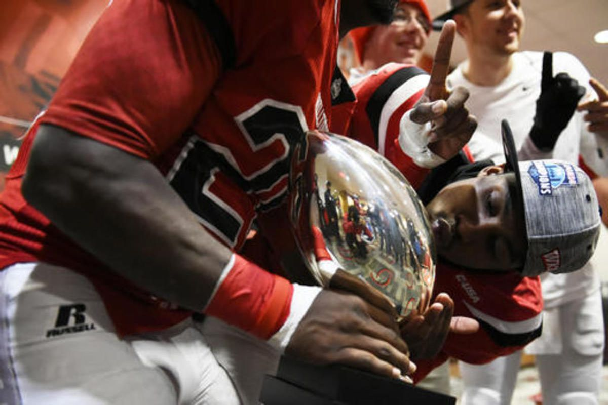 Western Kentucky wide receiver Nicholas Norris kisses the Conference USA championship trophy as they celebrate in the locker room after defeating Louisiana Tech 58-44 in an NCAA college football game, Saturday, Dec. 3, 2016 at L.T. Smith Stadium in Bowlin