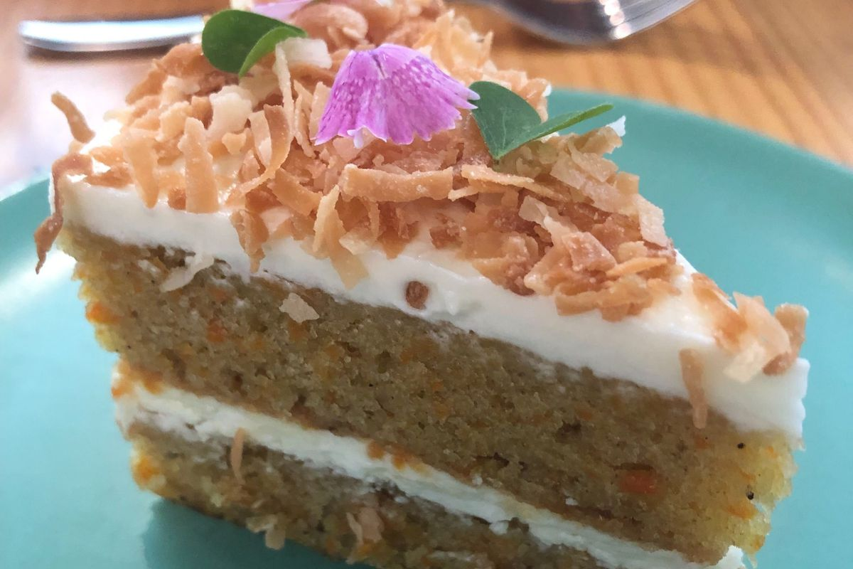 Two-layer cake covered with white icing, toasted coconut, and accented with a purple flower on a teal plate with a fork in the background.