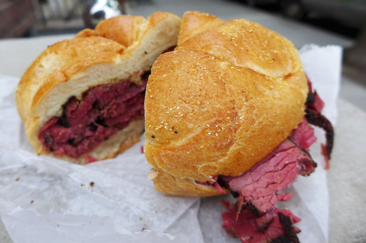 Pastrami peeping out of a dimpled kaiser roll, a shay sandwich.
