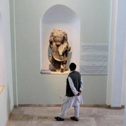 In this Wednesday, Aug. 29, 2012 photo, an Afghan visitor looks at a damaged statue at the National Museum of Afghanistan in Kabul. Right down to the power cuts that frequently plunge its artifacts into shadow, the National Museum of Afghanistan is a symbol of the country's recent hardships. Its building was shelled, looted and caught fire during the 1992s civil war. Taliban extremists later smashed many centuries- old statues.