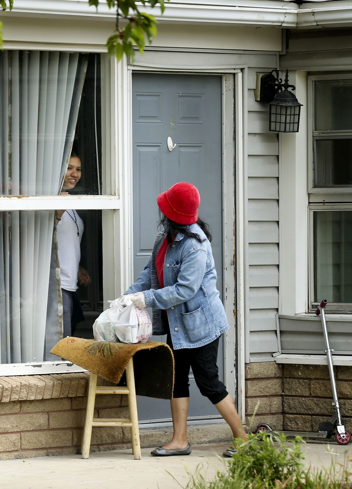 Elizabeth Montoya, right, delivers food to Macedonia Bonilla who was self-quarantining during the pandemic in the Glendale community of Salt Lake City on Wednesday, May 12, 2020.