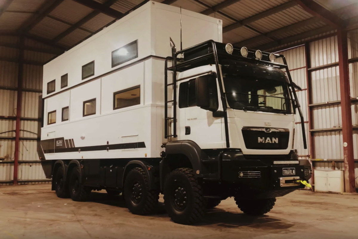 A white overland RV features giant tires, a burly black bumped, and a pop-up second story.