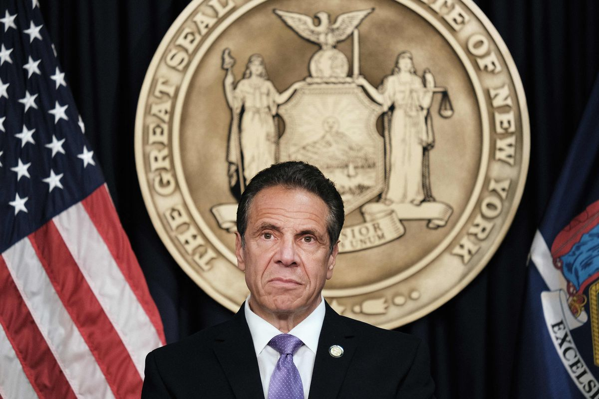 New York Governor Andrew Cuomo sits in front of the seal of the state of New York behind him, between the flags of the United States and New York.