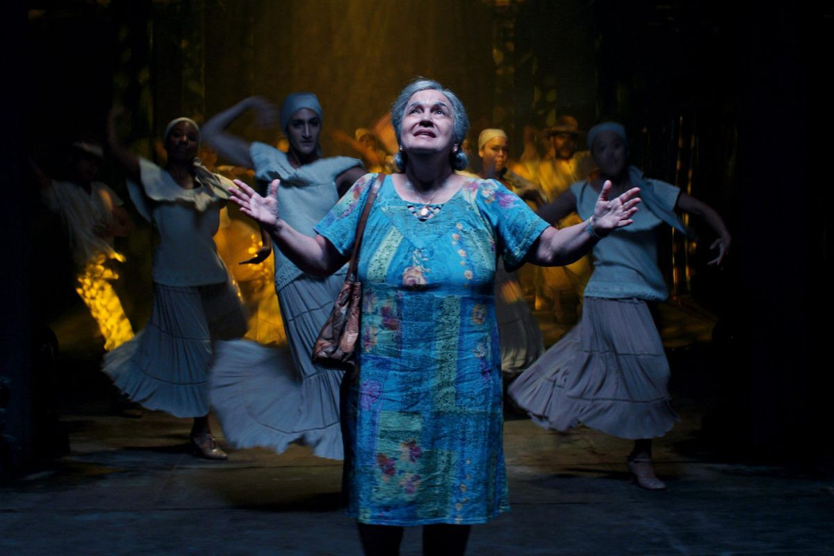 在蓝色花卉房子礼服的演员Olga Merediz在聚光灯下举起她的手,而拉丁蛋白舞者穿着在背景中的所有白色框架。