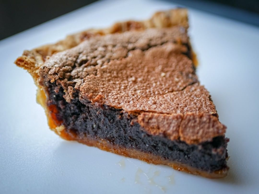 A slice of chocolate chess pie with a golden crust.