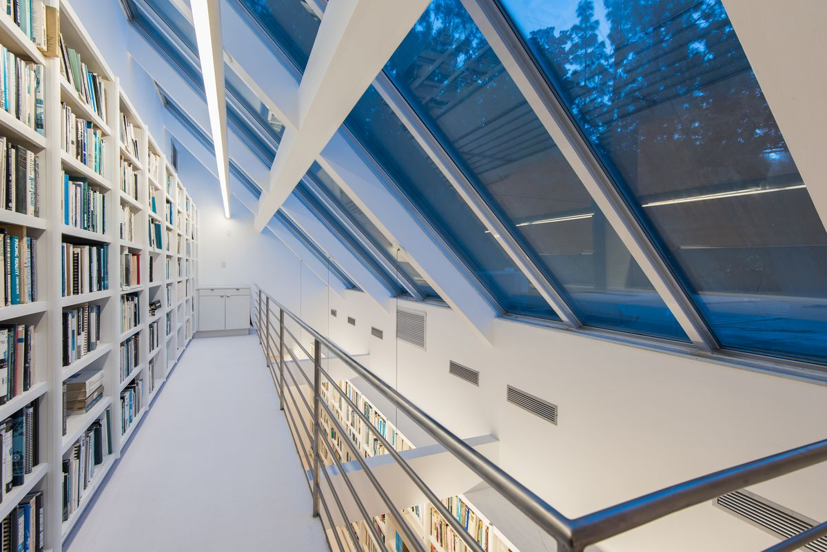 A room with a pitched glass ceiling and a long row of bookshelves