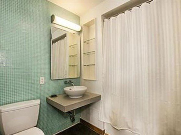 A bathroom with a basin sink and a shower with the curtain pulled forward.