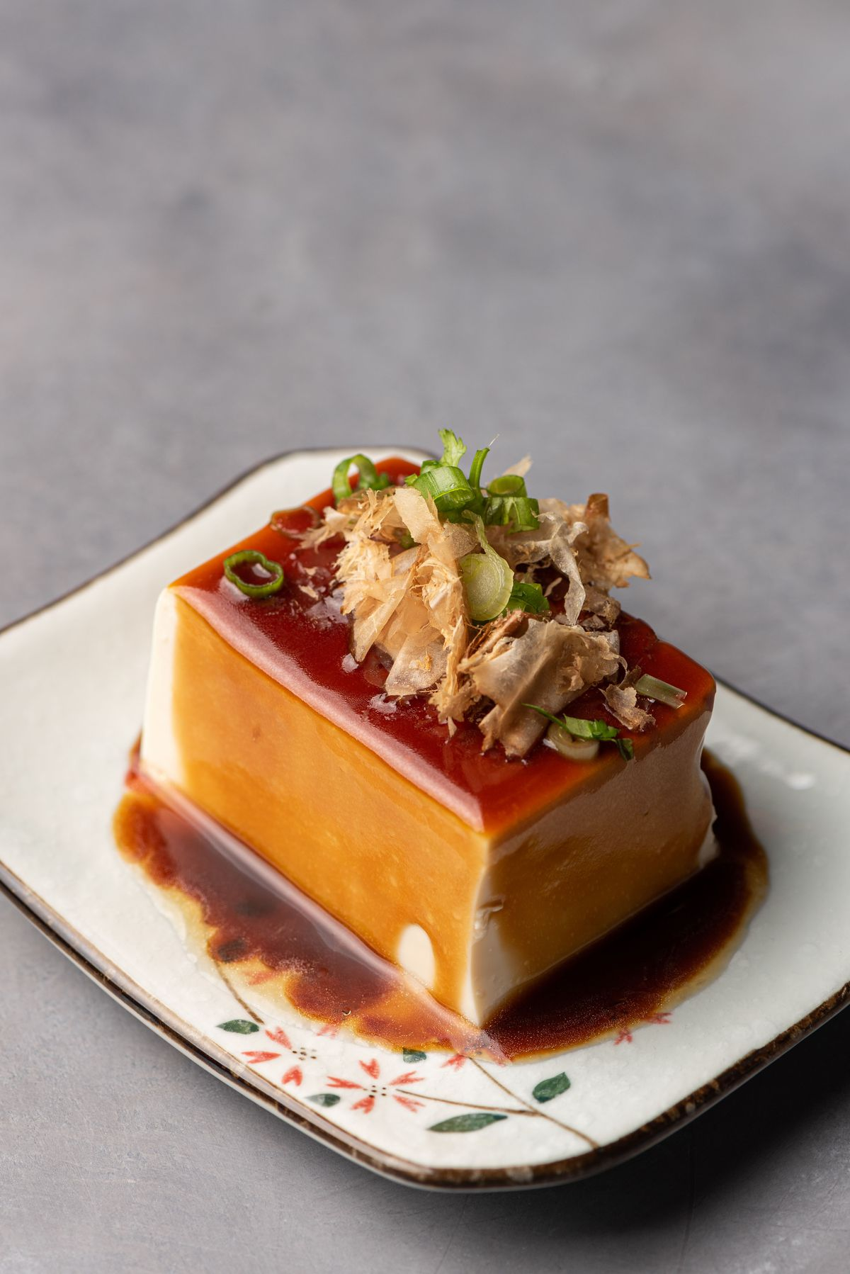 A large thick square of tofu with sauce.
