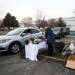Cars line up during the Big Brothers Big Sisters Holiday Drive Thru at a parking lot in Taylorsville on Thursday, Dec. 10, 2020.During the event, Littles (youths living in adversity), their Bigs (volunteer mentors) and their families were invited to pick up warm winter coats, gift cards and fun treats.