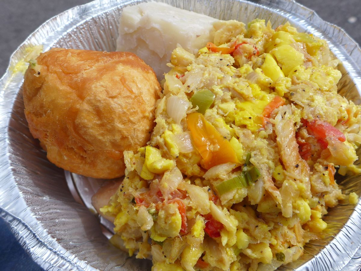 A metal container with something that looks like scrambled eggs and peppers, with a big fried dumpling on the side.