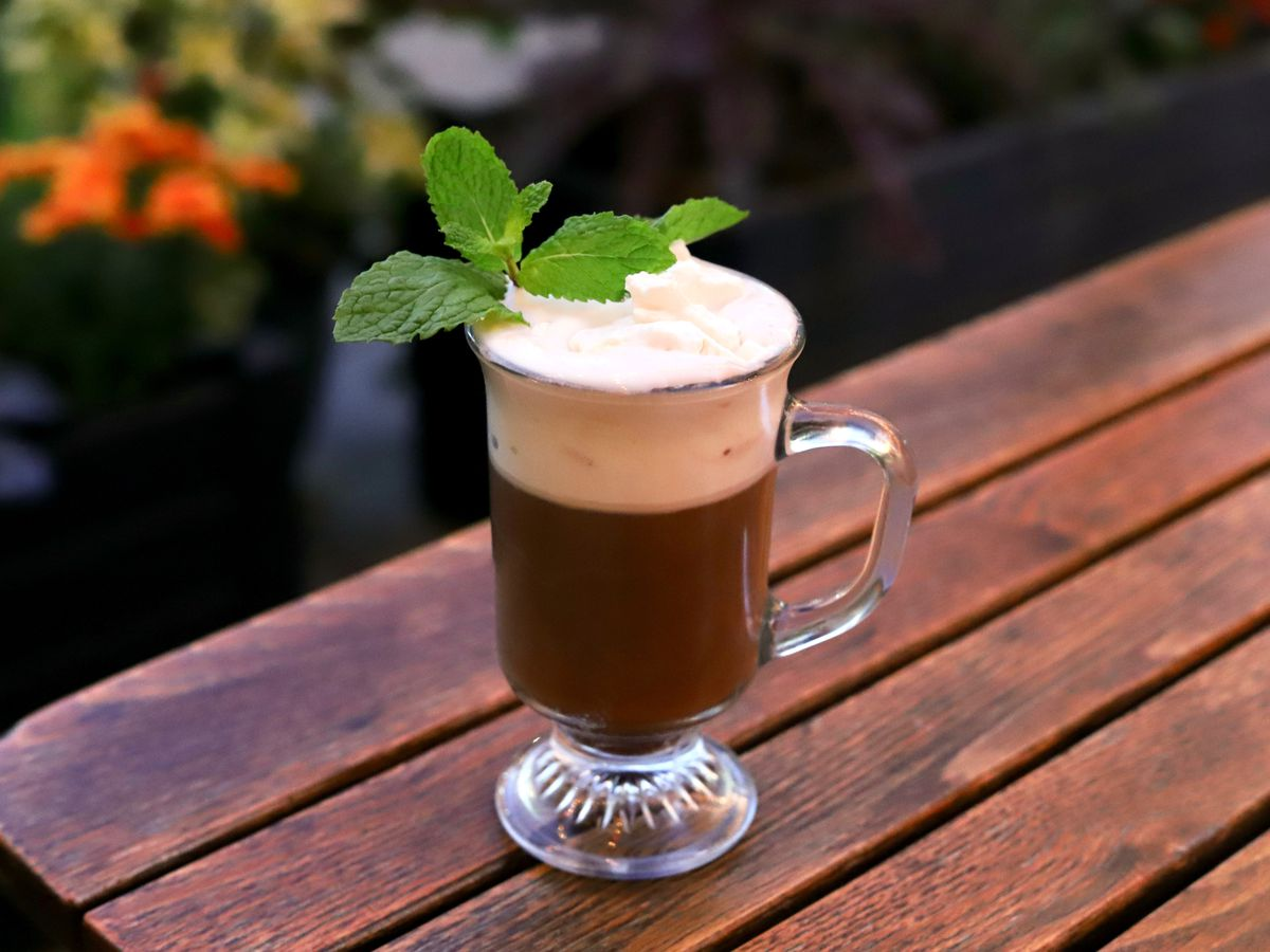 A spiked hot chocolate topped with whipped cream and fresh mint sits on a picnic table with potted plants visible in the background.