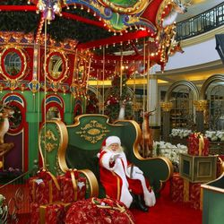 """Eighteen handmade, handpainted reindeer circle the inside of the carousel. """"You must be this tall to ride,"""" says Santa."""